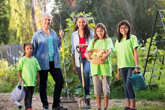 Four students and one adult gardener posing in front of garden with tools and vegetables.
