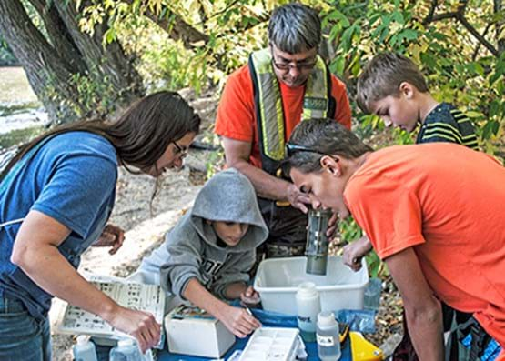 Three adults and two children huddle around table outside as they analyze water samples.
