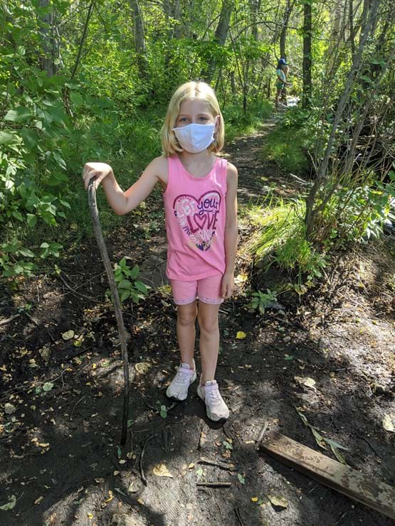 Little girl wearing a pink dress holding a walking stick